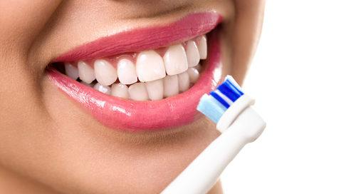 girl using electric toothbrush